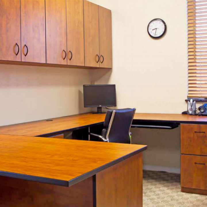 office with brown cabinetry and black chair