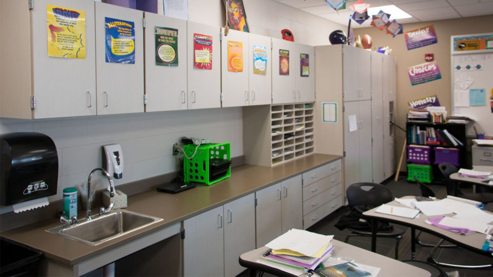 Classroom with desks and cabinetry and closets