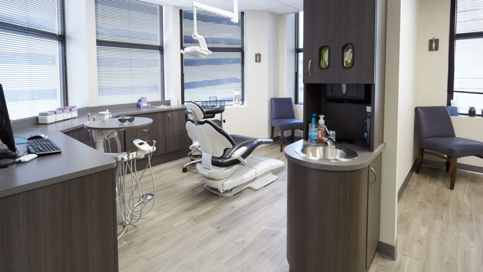 Dental exam room with dark cabinetry